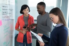 Female executive looking at graph with colleagues in background Royalty Free Stock Images