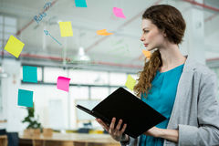 Female executive looking at sticky notes and holding folder Royalty Free Stock Photos