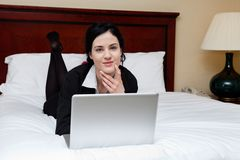 Female Executive Lying on Bed With Laptop Royalty Free Stock Images
