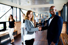 Female executive and male executive shaking hands in office hallway stock image