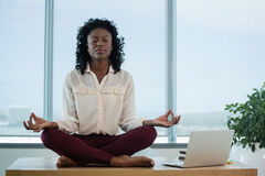 Female executive meditating on desk. In office Stock Image
