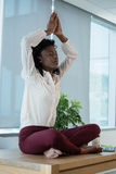 Female executive meditating on desk. In office Royalty Free Stock Image