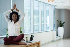 Female executive meditating on desk. In office Royalty Free Stock Photo