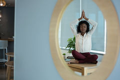 Female executive meditating on desk. In office Stock Photography
