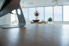 Female executive meditating on desk. In office Stock Photo