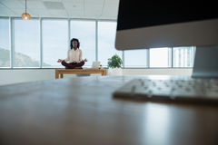 Female executive meditating on desk. In office Stock Images