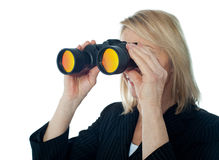 Female executive monitoring through binocular Stock Photo