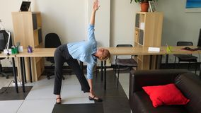 female executive performing stretching at her workplace in