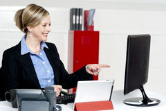 Female executive pointing at computer screen Royalty Free Stock Image