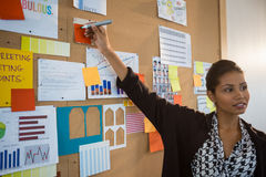 Female executive pointing at sticky note on bulletin board Stock Photography