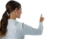 Female executive pretending to touch an invisible. Screen against white background Stock Photo