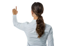 Female executive pretending to touch an invisible screen against white background. Rear view of female executive pretending to touch an invisible screen against Stock Image