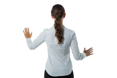 Female executive pretending to touch an invisible screen against white background. Rear view of female executive pretending to touch an invisible screen against Royalty Free Stock Photos