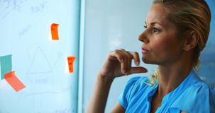 Female executive reading sticky notes on glass board. In office stock video footage