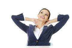 Female executive relaxing with hands behind head Royalty Free Stock Image