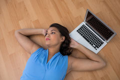 Female executive relaxing with hands behind head on the floor Royalty Free Stock Image