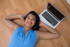 Female executive relaxing with hands behind head on the floor Royalty Free Stock Images