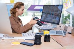 Female executive reviewing captured photograph at her desk Royalty Free Stock Images