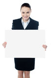 Female executive showing blank billboard to camera Stock Photo