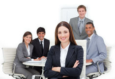 Female executive sitting in front of her team stock photography