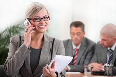 Female executive speaking on the phone. Female executive with team in background Royalty Free Stock Photos