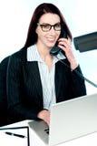 Female executive speaking on phone Royalty Free Stock Photos