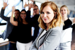 Female executive standing in front of colleagues Stock Photo