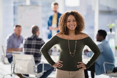 Female executive standing with hands on hip in the office Stock Images