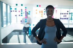 Female executive standing with hands on hip in office royalty free stock images