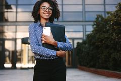 Female Executive Standing Outside Office Building Stock Photo