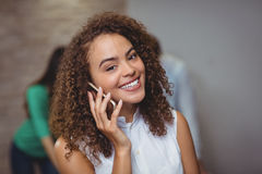 Female executive talking on mobile phone in office Stock Image