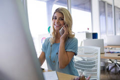 Female executive talking on mobile phone while working at her desk Stock Photos