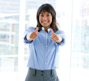 Female executive with thumbs up standing Stock Photography