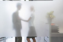 Female Executive Touching Male Colleague Behind Translucent Wall. Side view of a female office worker touching male colleague behind translucent wall in office Stock Photos