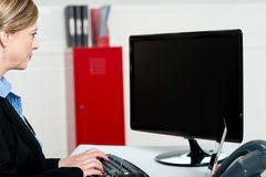 Female executive typing and looking at lcd screen Royalty Free Stock Photos