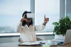 Female executive using virtual reality headset at desk Stock Image