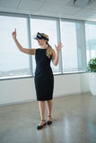 Female executive using virtual reality headset in office Royalty Free Stock Image