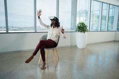 Female executive using virtual reality headset in office Stock Photo