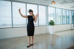 Female executive using virtual reality headset in office Stock Images