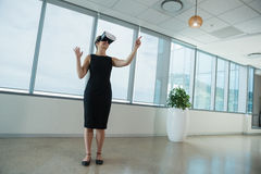 Female executive using virtual reality headset in office Stock Photos