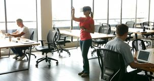 Female executive using virtual realty headset while her colleagues working at desk 4k. Female executive using virtual realty headset while her colleagues working stock footage