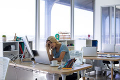 Female executive working at her desk. Stressed female executive working at her desk in office stock photos