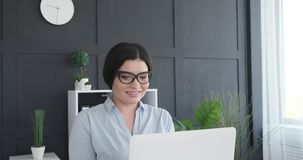 Female executive working on laptop. Smiling female executive working on laptop at office stock video