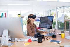 Female executive working on laptop while using virtual reality headset. In office Royalty Free Stock Image