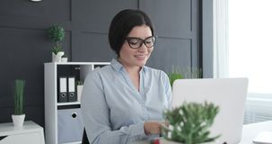 Female executive working on office laptop. Happy female executive working on laptop at office stock video footage
