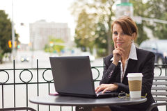 Female executive working outdoors at cafe. A female executive working outdoors at cafe Stock Photos