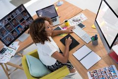 Female executive working over graphic tablet at her desk Royalty Free Stock Photo