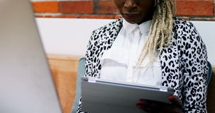 Female executive working on personal computer while holding digital tablet. In office stock footage