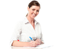 Female executive writing business report Royalty Free Stock Image