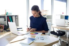 Female executive writing in diary at her desk Royalty Free Stock Images